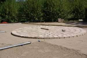 Screed pipe with MAKO FinCap screed chairs leveling sub-grade for pavers